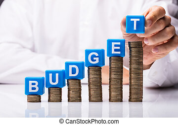 Person Placing Cubic Blocks With Budget Word On Stacked Coins