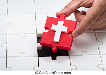 Person placing holy cross symbol piece into jigsaw puzzle