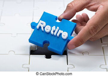 Person placing last retire piece into jigsaw puzzle
