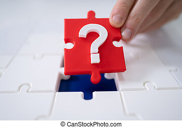 Person Placing Question Mark Piece Into Jigsaw Puzzle