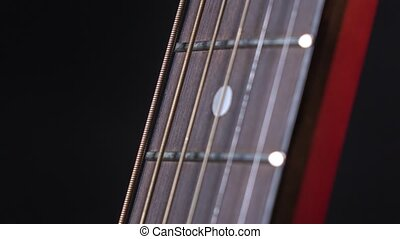 Person play strings of acoustic guitar, on black, close up