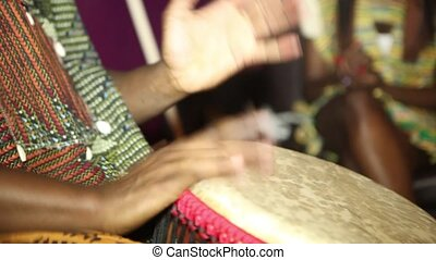 person playing on Jambe Drum no face. Closeup of man's hands drumming out a beat on an African skin-covered djembe hand drum.