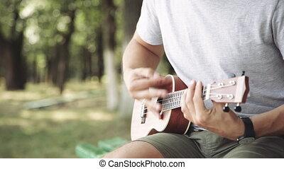 Person playing on little ukulele