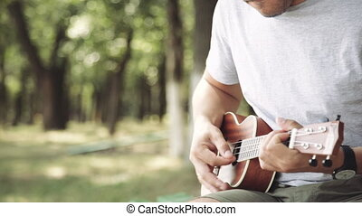 Person playing on little ukulele