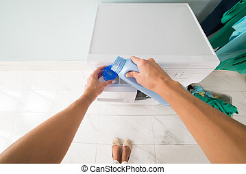 Person Pouring Detergent In A Lid