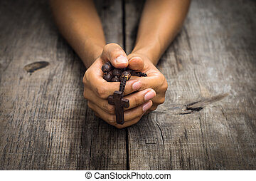 Person Praying - A person praying holding a rosary in the...