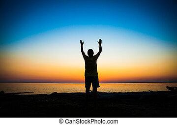 Person Praying at Sunset