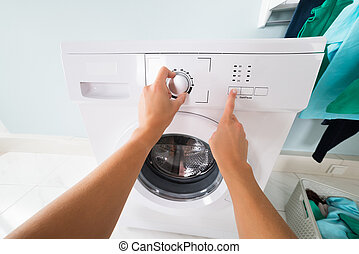 Person Pressing Button Of Washing Machine
