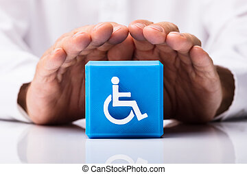 Person Protecting Cubic Block With Disabled Icon