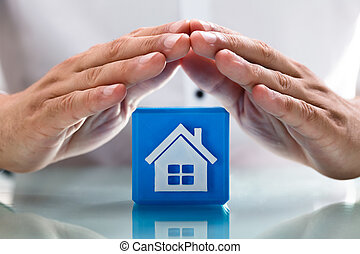 Person protecting cubic block with house icon