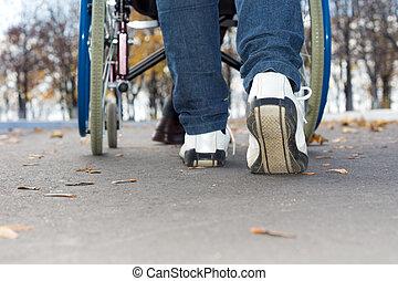 Person pushing a wheelchair down the street