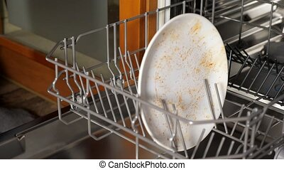 person puts dirty dishes and cutlery into dishwasher closeup...