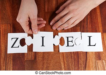 person puzzling the german word ZIEL