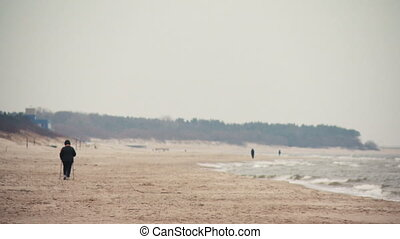 Person recreation nordic walking on the beach in Palanga, Lithuania.