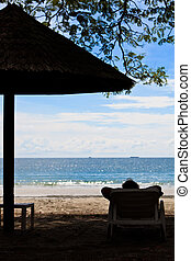 Person relaxing on the beach of a tropical island