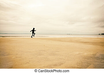 Person running on beach - Person running on the beach a cold...