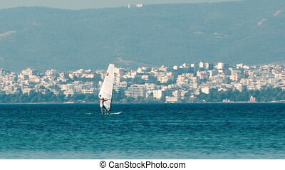 Person sailboarding offshore on a calm ocean with a town...