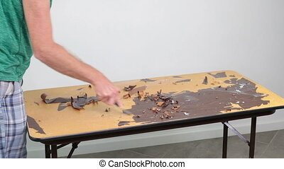 Person Scraping a Particle Board and Metal Tabletop of an Old Sticker