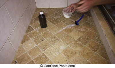 Person Scrubbing Shower Tile Floor - One adult male cleaning...