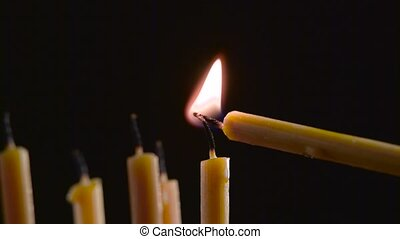 Person sets a candle in the temple. Black background -...