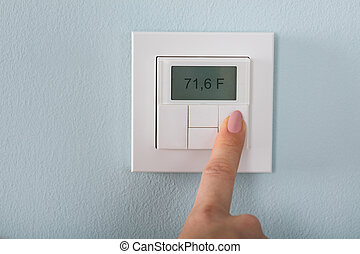 Person Setting The Thermostat