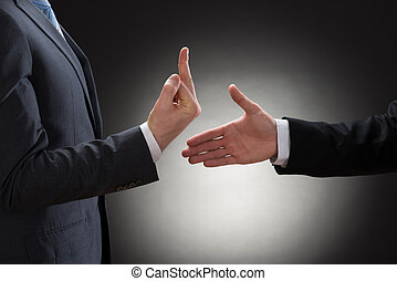 Close-up Of A Person Trying To Shake Hand With A Person Showing Fuck Gesture