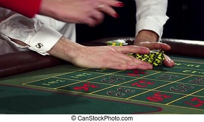 Person sitting at the roulette table, placing their bets. Black