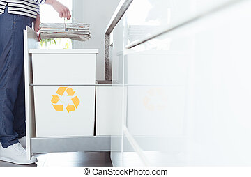 Person sorting paper in kitchen