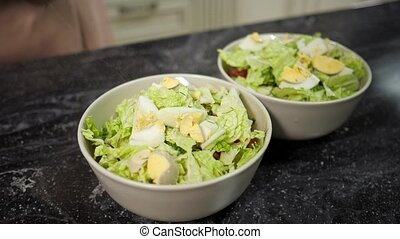 person spices fresh salad in bowls with fragrant seasonings...