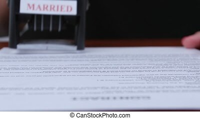 Person stamps the document of marriage by a rectangular seal. Close up