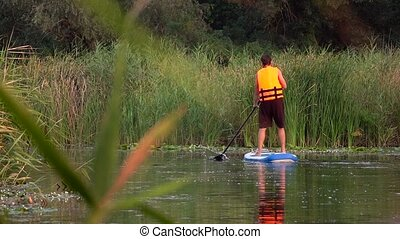 Person stand up paddle boarding and paddles along the river...