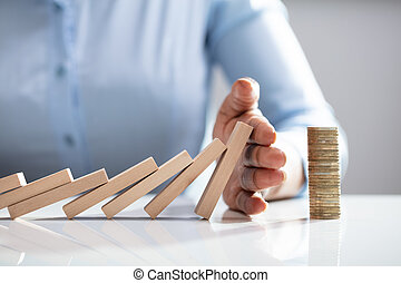 Person Stopping Dominos From Falling With Stacked Coins