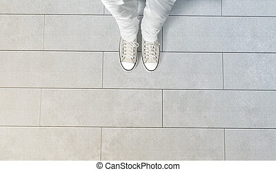 Person taking photo of his feet stand on concrete floor,...