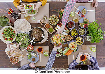 Person taking picture of food while eating meal with friends