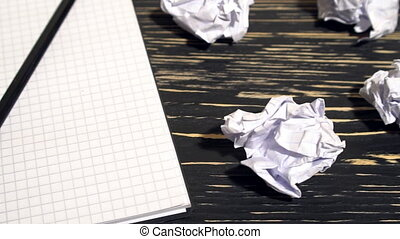 Person throwing a lot of crumpled paper on a desk, close-up....