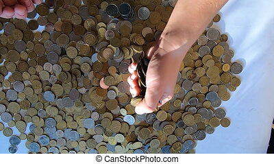 Person two hands rakes coins on table, pours spills from handful to surface on sunny day close-up. Money falling slow motion. Concept global economic crisis, financial crisis default pouring recession