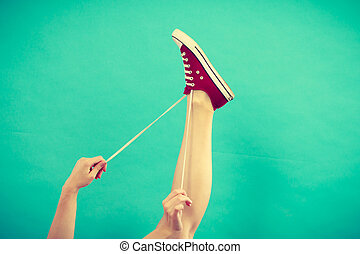 Person tying red sneaker with foot up