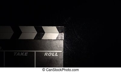 Person uses movie clapper board on black close up - Person...