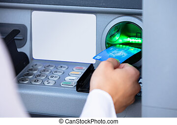Person Using Card To Withdraw Money From ATM Machine