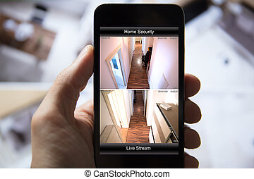 Person Using Home Security System On Mobile Phone