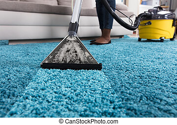 Person Using Vacuum Cleaner For Cleaning Carpet