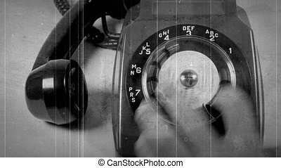 Black and white vintage celluloid scratched footage of hand turning wheel on old fashioned landline telephone, telephone call, dialling, vintage technology