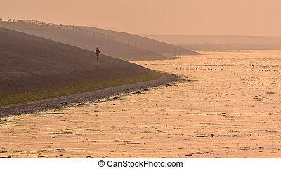 Person walking on Sea dike in orange haze
