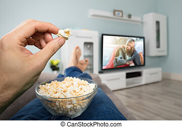 Person Watching Movie While Eating Popcorn