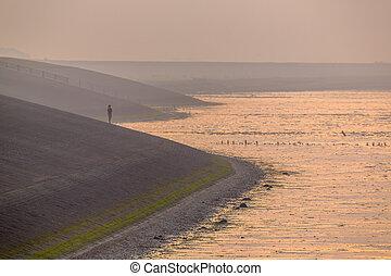 Person watching sunset from Sea dike in orange haze
