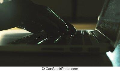 Person wearing black gloves typing on laptop keyboard....