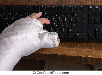 Person with arm cast typing on a keyboard - Person wearing...