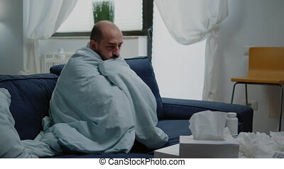 Person with flu feeling cold and shivering wrapped in blanket. Sick man having chills and fever symptoms while trying to get warm with cover, to cure illness with medicaments on table.
