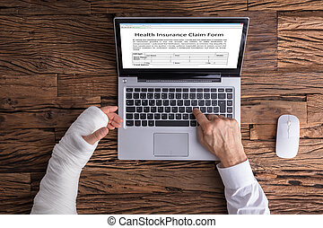 Person With Hand Injury Filling Health Insurance Claim Form
