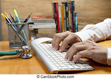 Person with hand on keyboard at an office desk